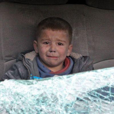 en gråtande pojke sitter i en bil efter en flygräd i staden Ariha i Idlib i Syrien.