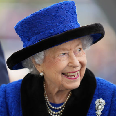 Drottning Elizabeth ler och tittar åt sidan. Hon har på sig en blå kavaj och en hatt i samma nyans.