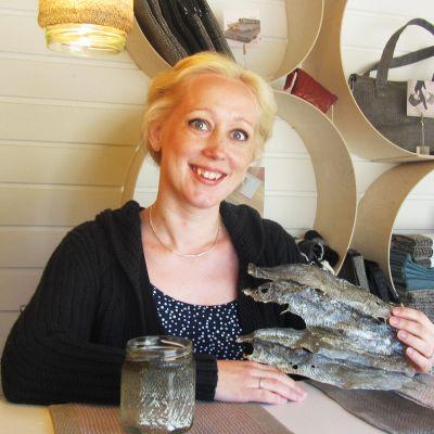 Kuvassa kalannahkoista käsitöitä tekevä Satu Somero.