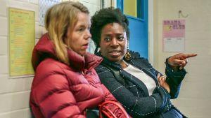 Sarjan Julia (Anna Maxwell-Martin) ja Meg (Tanya Moodie) istuvat koulun käytävällä penkillä.