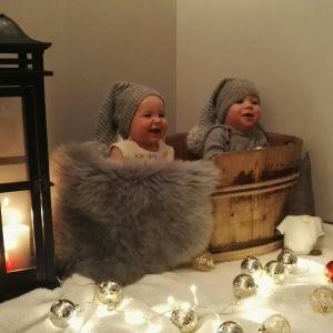 Två små barn sitter i en korg med tomteluva på