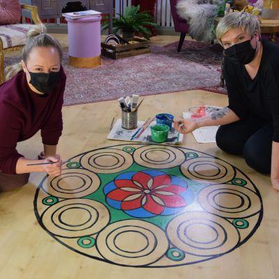 Två blonda kvinnor med ansiktsmasker som sitter på golvet i ett rum och målar en stor mandala på laminatgolvet.