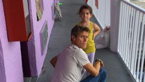 Bobby (Willem Dafoe) på knä framför Moonee (Brooklynn Prince) vid huset där de bor.