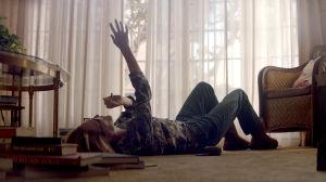Gloria Bell ligger på golvet och röker gräs.