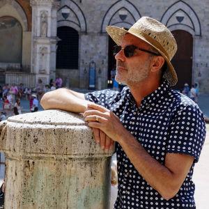Olkihattuinen aurinkolasinen mies nojaa pylvääseen italialaisen pikkukaupungin torilla kauniina kesäpäivänä.
