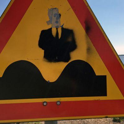 """Liikennemerkki """"Kuoppia tiessä"""", joku töhrinyt merkkiä."""