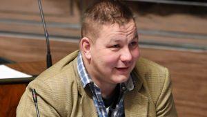 Juha Mäenpää leende i riksdagens plenisal