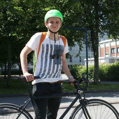 Axel Nurmio står bredvid sin cykel.