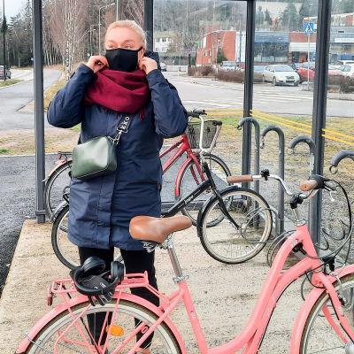 En kvinna sätter på sig ett munskydd. Hon står utomhus vid en cykelställning.