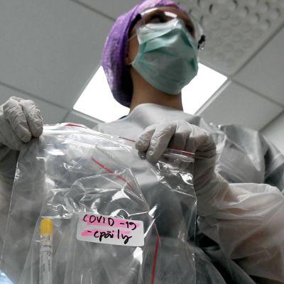 Laboratorieskötare med misstänkt covid-19 provrör