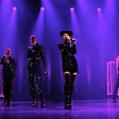 A cappella-gruppen Fork på scenen i svarta kläder och lila scenljus.