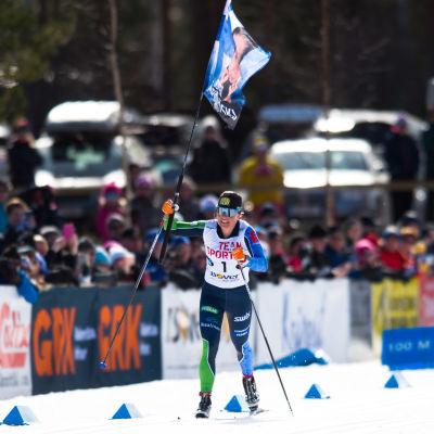 Krista Pärmäkoski viftar med flaggan då hon åker i mål.