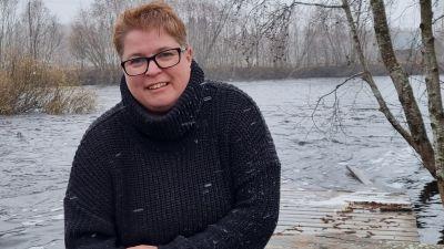 Kvinna i mörk tröja sitter på en brygga vid ett vattendrag.