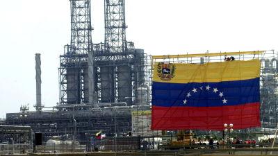 Oljearbetare hänger upp jätteflagga vid statliga oljebolaget PVDSA
