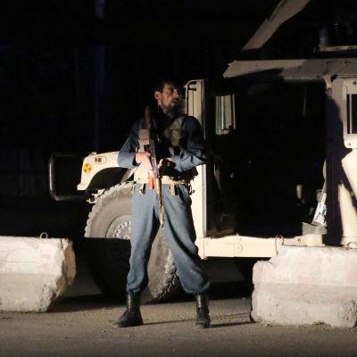 Afghansk polis säkrar en väg i Kabul efter bombdåd.