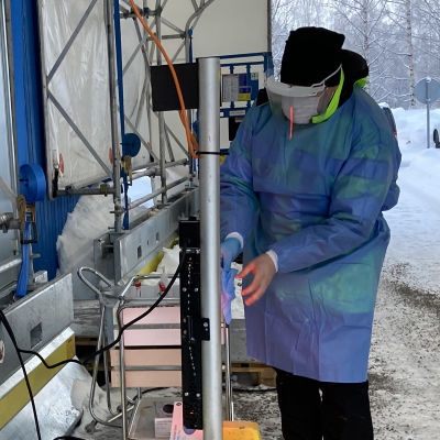 Kuvassa koronatestaaja lämmittelee käsiään infrapunalämmittimen ääressä