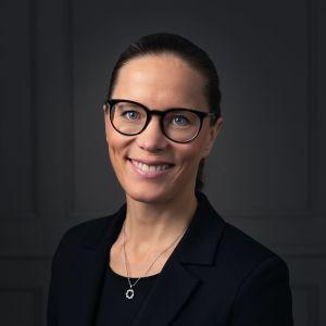 en kvinna i mörka kläder, uppsatt hår och glasögon ler med tänderna fram