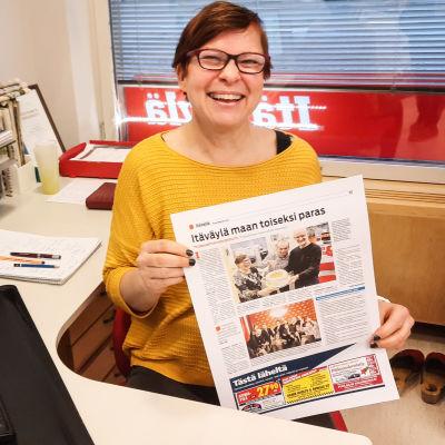 En kvinna i gul tröja sitter vid ett skrivbord. Hon håller upp en tidningssida mot kameran och ler.