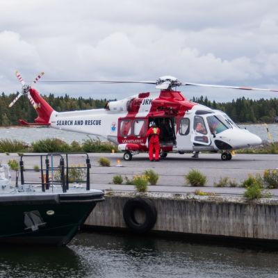 En sjöräddningshelikopter står parkerad på en pir. I förgrunden en förtöjd gränsbevakningsbåt.