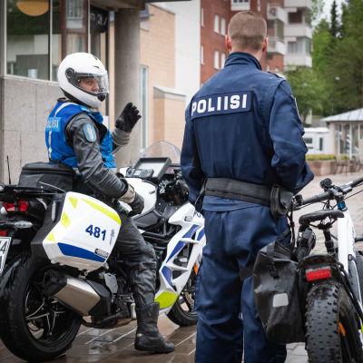 En polis sitter på en motorcykel, medan en annan polis står vid en cykel.