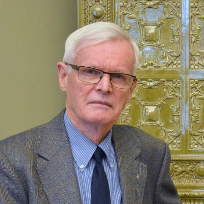 En man i kostym och glasögon står framför en guldfärgad kamin.
