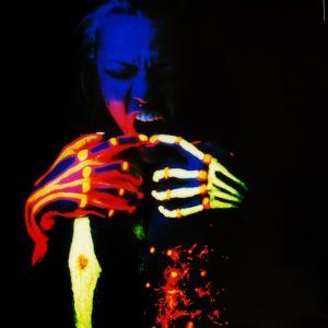 Mustaa taustaa vasten otettu kuva, jossa henkilön kasvot ja raajat on maalattu neonvärein.