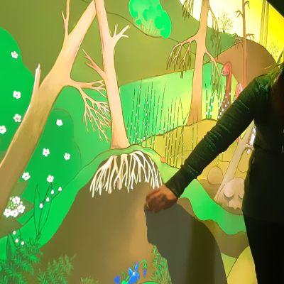Nainen koskettaa virtuaaliseinää, jossa näkyy puiden runkoja ja juuria.