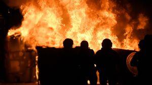 Brand under protester i Barcelona. Mot lågorna ser man siluetten av tre huvuden.