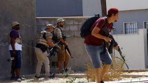 En civilklädd milisman springer över en gata samtidigt som hans kamrater tar skydd bakom en vägg
