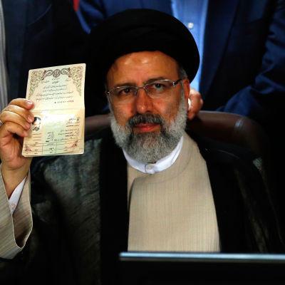 Den konservativa ledaren Ebrahim Raisi visar upp sin identitetshandling efter att han registrerade sig som presidentkandidat. Han blir president Rouhanuis främsta utmanare