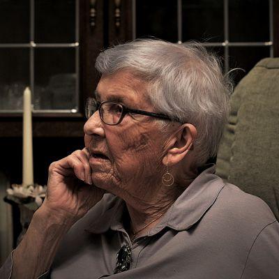 Äldre kvinna framför en bokhylla blickar ut från kameran.