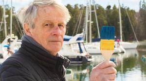 Ole Sandman med målarpensel i handen i hamnen med segelbåtar