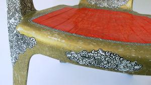 Den vita plaststolen pyntad i Rokoko-stil med sprayfärg. Detalj.