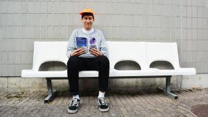 Kasper Strömman läser sin bok på vit bänk