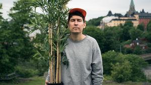 Kasper Strömman med krukväxt utomhus.