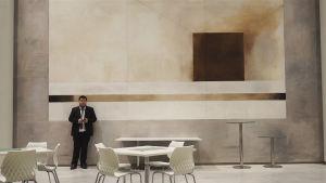 Musikern Thomas Enroth ensam i svart kostym i stor sal med mobiltelefon i handen