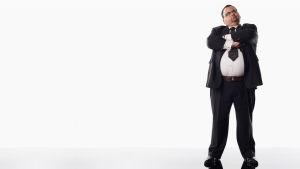 Överviktig man i svart kostym i helprofil styår till höger på bilden med vit bakgrund.