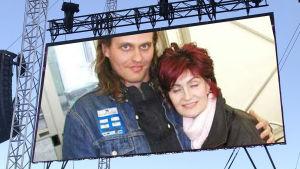 Lasse Grönroos och Sharon Osbourne poserar tillsammans på Ozzfest i England 2002. Fotot inklippt på Rockfests stora skärm.