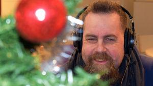 Stan Saanila tittar fram bakom julgran i förgrunden. Han har hörlurar på huvudet och ler.
