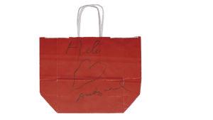 Röd tygkass med texten Heli ett hjärta och signaturen Andy Warhol som Warhol gett åt Heli vaaranen.