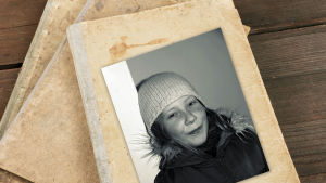 Svartvitt fotografi på Rosanna Fellman som elvaåring med vit vintermössa.