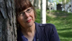 Dramaturgen Camilla Thelestam lutar mot en tall med sommargrönska i bakgrunden.