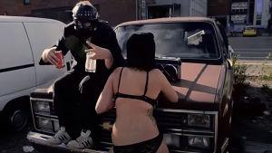 Sairas T med lättklädd kvinna på biltak.