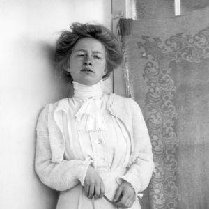 Edith Södergran mot tapet i lång vit klänning. Måttband i handen. Uppsatt hår. blicken snett nedåt.