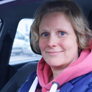 Blond kvinna sitter inne i en bil bakom ratten. Hon tittar in i kameran och småler.