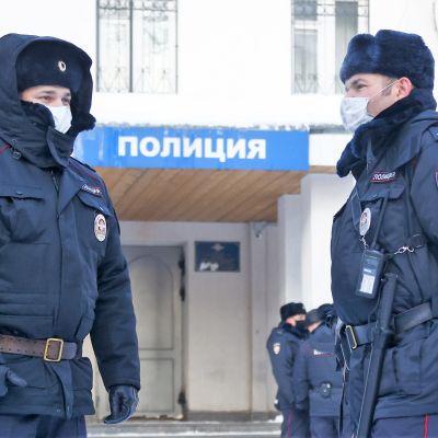 Kaksi poliismiestä seisoo poliisiaseman edustalla. Molemmilla on karvalakit päässä, toinen on nostanut hupun lakin päälle. Miehillä on suojamaskit.