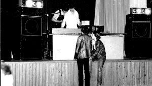 En mycket ung Måns Strömberg med kompis som dj på svartvitt foto. Två tjejer står framför scenen.