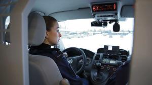 En kvinnlig polis i sin patrulleringsbil.