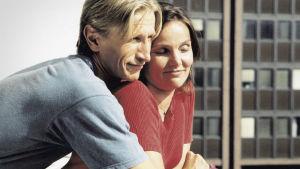 Nainen ja mies halaavat parvekkeella hymyileväisinä.