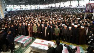 Människor samlade till en begravning. Kistorna i förgrunden.